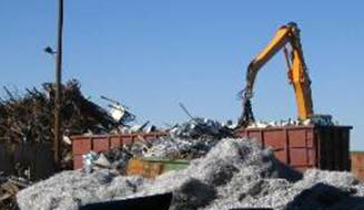 Crane unloading scrap from a roll-off container